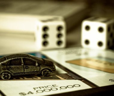 Part of the Monopoly game board and a car figurine